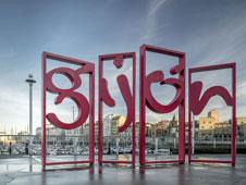 Una escultura con el nombre de la ciudad recibe al visitante en el puerto deportivo. | Fotograf�as: Turismo de Gij�n